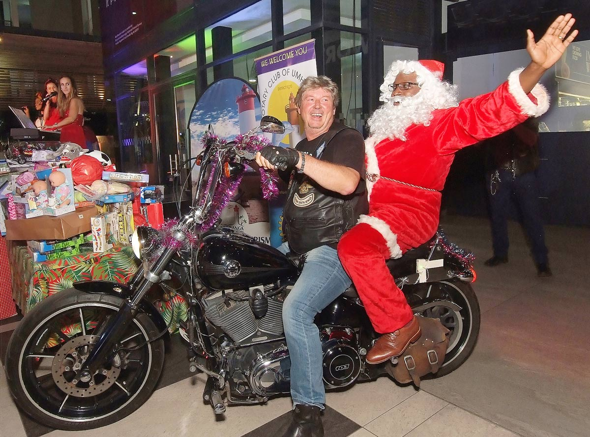 FEATURED IMAGE: Andre Roodt of the Durban Free Chapter of the Harley Owners Group arrives at the carols concert with a pillion passenger in a million, Santa Claus. In the background are some of the toys donated by carolers to needy kids and the entertainers on the Granada Square stage. Pictures: ROY REED